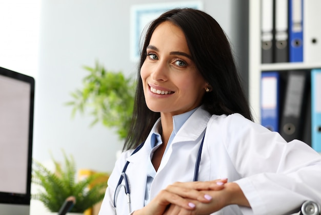 Mature female gp sitting at working table arms crossed