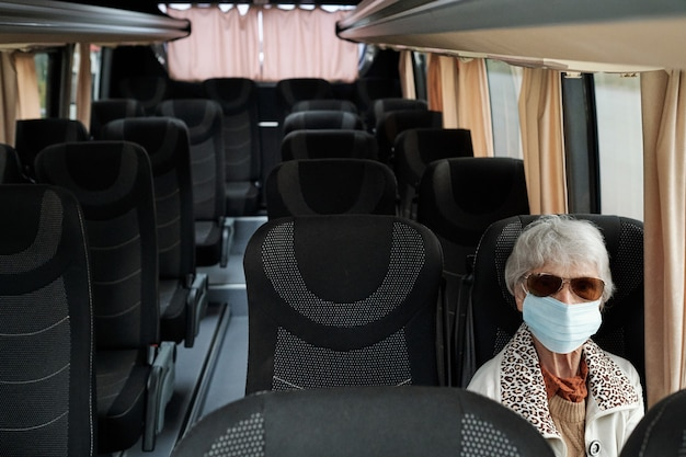 Зрелая женщина в защитной маске сидит на сиденье внутри автобуса