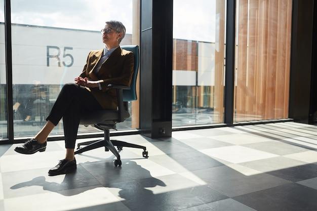 椅子に座って大きなオフィスの窓に対して何かを考えている成熟した女性リーダー