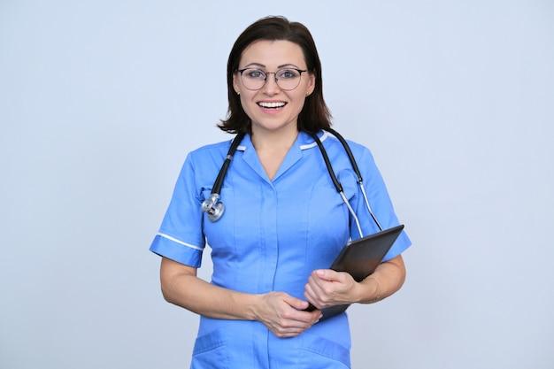 デジタルタブレット、灰色の笑顔の看護師と成熟した女性医療従事者