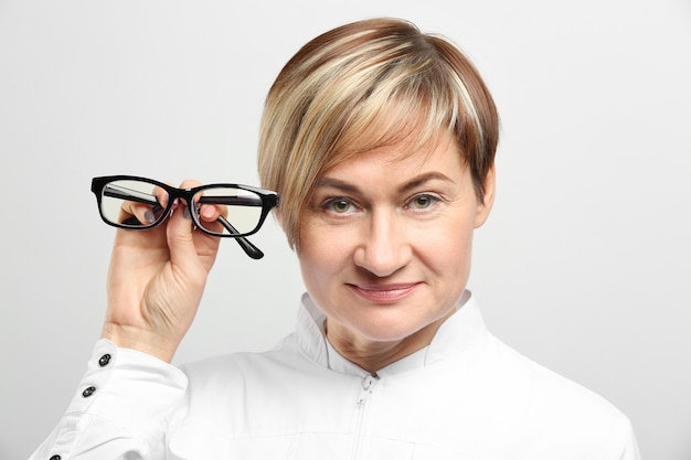 Mature female ophthalmologist with glasses on white background