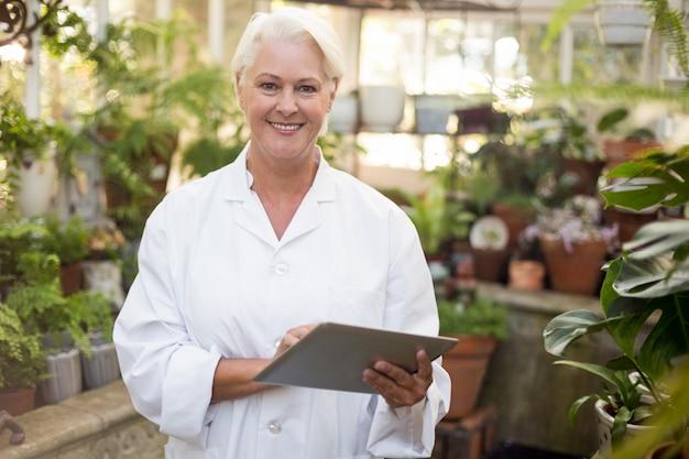 デジタルタブレットを使用しながら笑みを浮かべて成熟した女性科学者