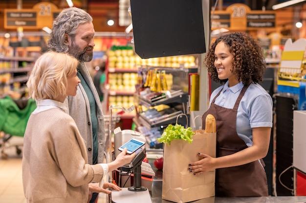 Зрелая женщина со смартфоном платит за продукты в супермаркете, стоя рядом с мужем перед счастливым молодым кассиром