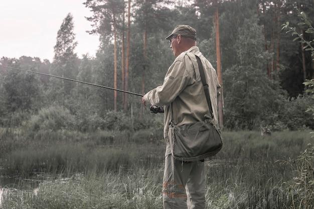 森で釣りをし、釣り竿を持っている成熟した漁師。