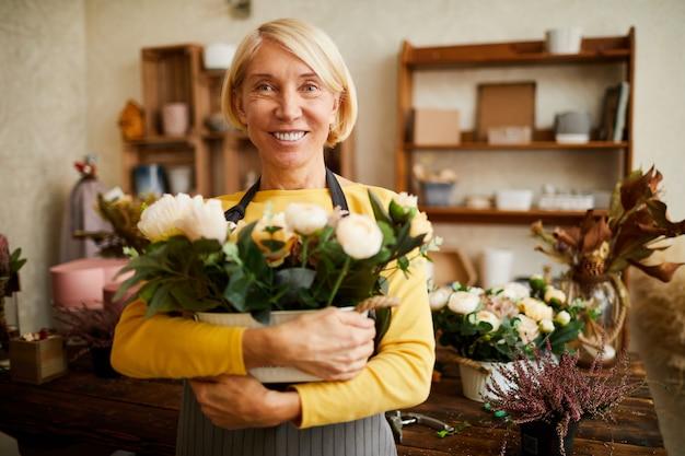 成熟した花屋の花束を保持