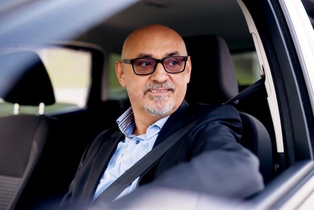 スーツを着た成熟した専門のエレガントなビジネスマンが車を運転し、窓の外を見ています。