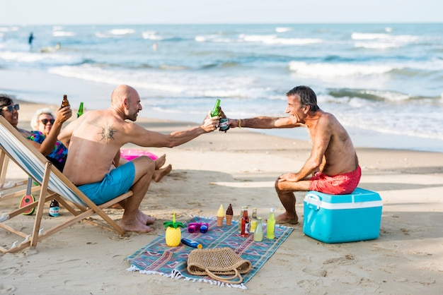 Mature friends having beers at the beach