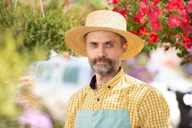 Mature gardener in hat and apron standing among flowers in bloom while working in greenhouse