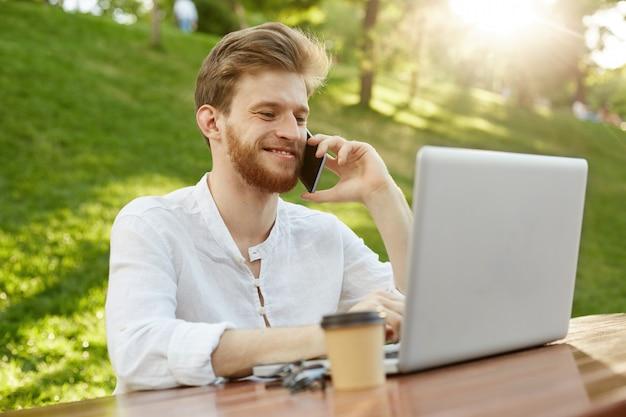 Зрелый рыжий красавец с ноутбуком в парке