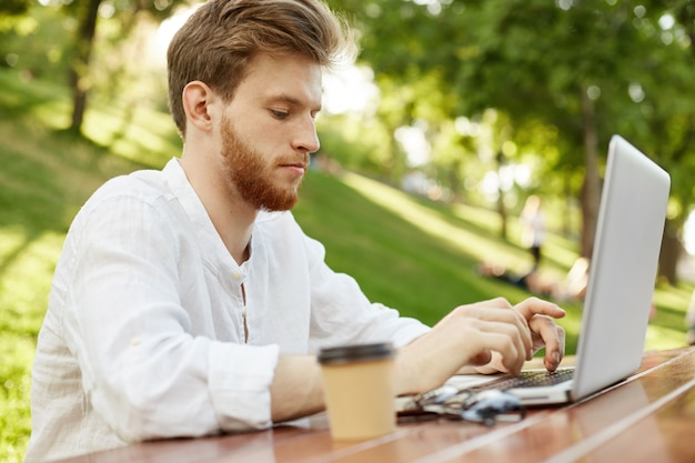 Mature ginger handsome man with laptop computer in the park