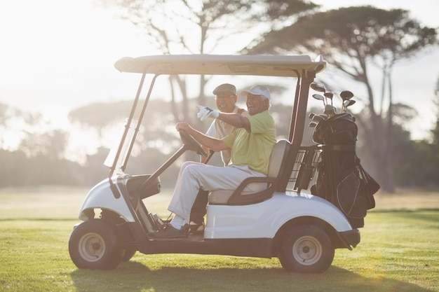 Mature golfer man pointing while sitting by friend
