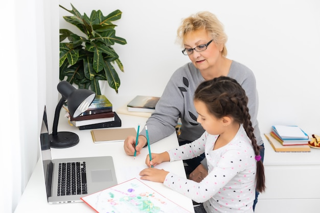 Пожилая бабушка помогает ребенку с домашним заданием дома. довольная старая бабушка помогает своей внучке учиться в гостиной. маленькая девочка пишет на тетради со старшим учителем, сидящим рядом с ней