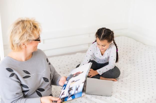 家で宿題を手伝う成熟した祖母。居間で勉強している孫娘を手伝ってくれるおばあちゃんに満足。彼女の隣に座っている先輩の先生とノートに書いている少女