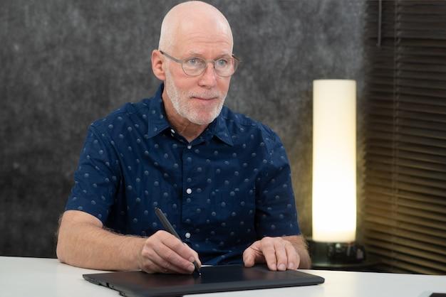 디지털화 된 펜을 사용하는 성숙한 그래픽 디자이너