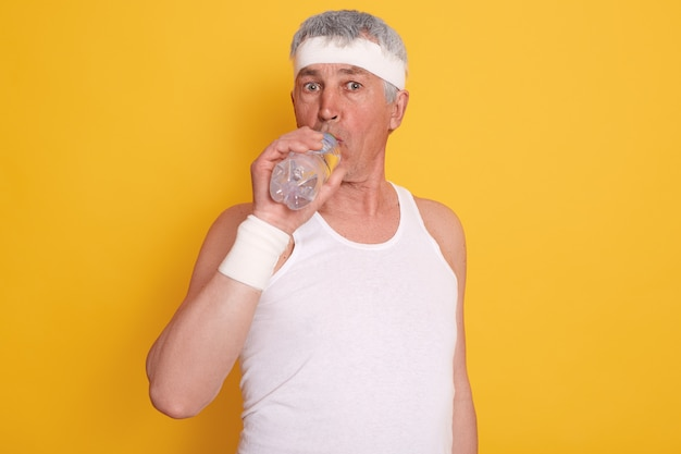 Mature grey haired male dresses white headband and sleeveless t shirt, drinking water during physical exercising,