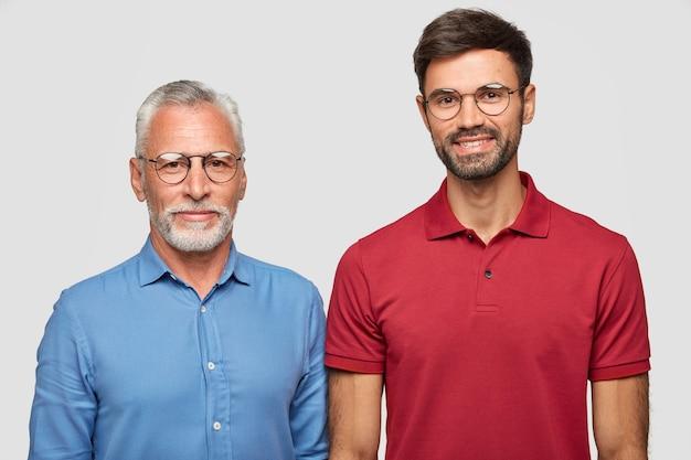 L'uomo maturo dai capelli grigi e suo figlio adulto stanno contro il muro bianco, hanno espressioni compiaciute dopo l'incontro, indossano occhiali rotondi, essendo una famiglia amichevole. persone e concetto di generazione