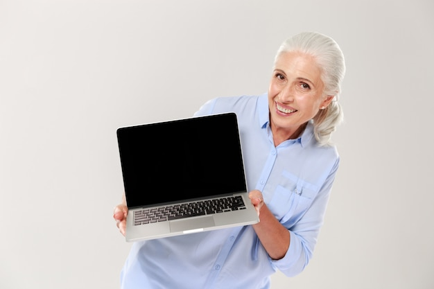Mature grey-haired woman smiling and showing blank screen of laptop isolated