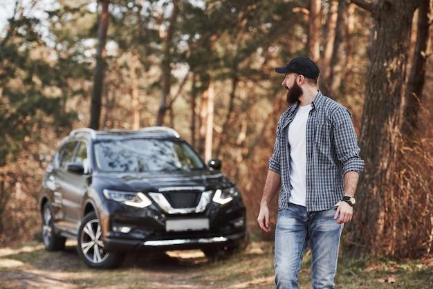 成熟した男は散歩をしています。森の中の彼の真新しい黒い車の近くのひげを生やした男。休暇の概念