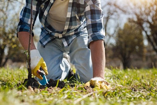 손잡이 토양 국자를 사용하여 퇴비로 잔디를 덮는 격자 무늬 셔츠에 성숙한 남자 프리미엄 사진