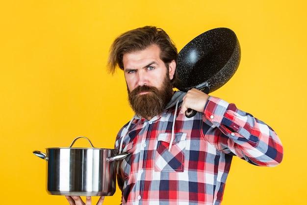 鍋と市松模様のシャツの成熟した男。スタイリッシュな男性が料理をしに行きます。口ひげを生やしたひげを生やした男は台所用品を使用します。健康な食生活。焦げ付き防止面。シェフが夕食を作る。設計によるケータリング。