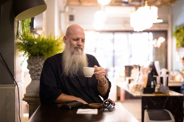 Зрелый красивый лысый бородатый мужчина пьет кофе в кафе