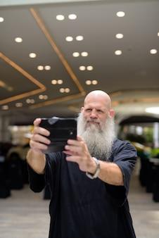 Зрелый красивый лысый бородатый мужчина делает селфи в городе на открытом воздухе