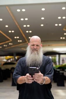 Зрелый красивый лысый бородатый мужчина разговаривает по телефону в городе на открытом воздухе