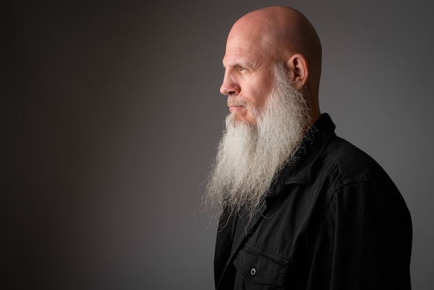 Mature handsome bald man with long gray beard on white