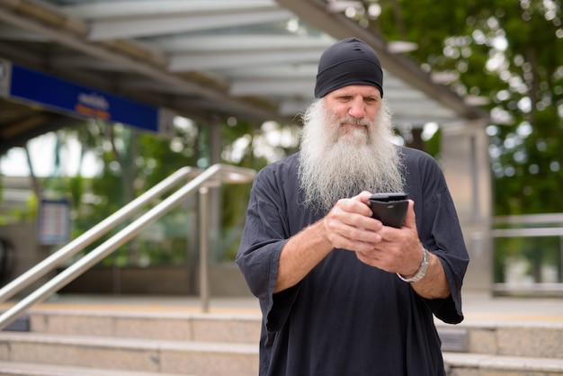 Mature handsome bearded hipster man using phone outside the subway train station