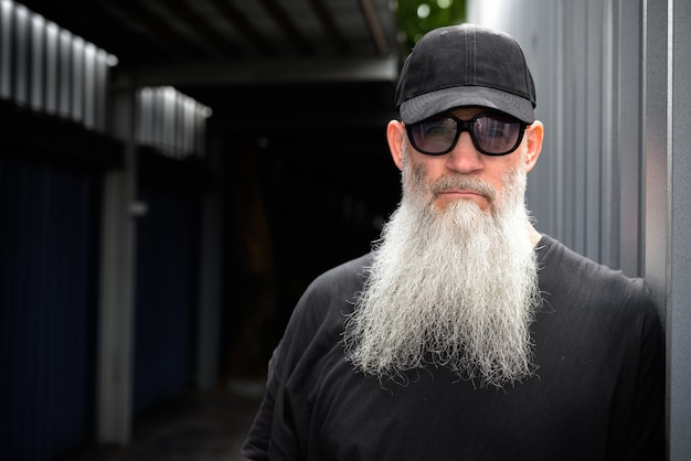 通りでキャップとサングラスを持つ成熟したハンサムなひげを生やしたヒップスターの男