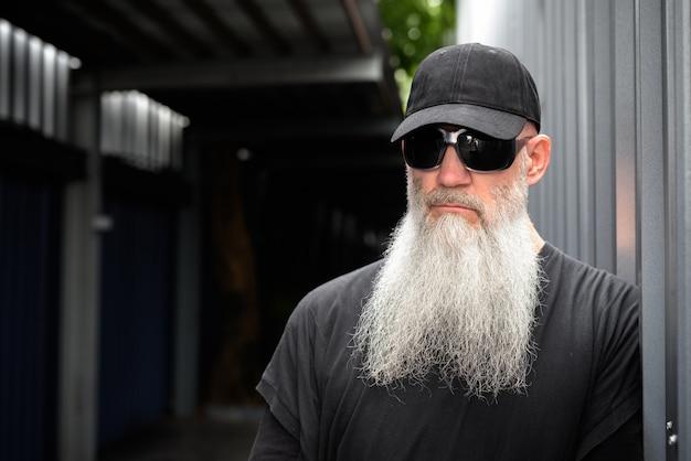 通りで考えているキャップとサングラスを持つ成熟したハンサムなひげを生やしたヒップスターの男