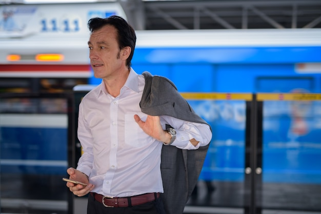 屋外の駅で成熟したハンサムなビジネスマン
