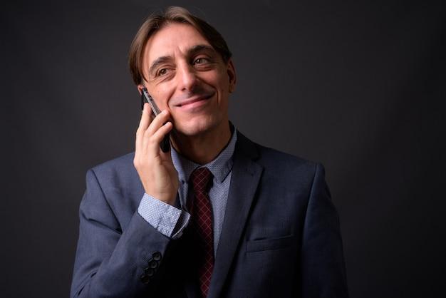 灰色の壁に対して成熟したハンサムなイタリアの実業家