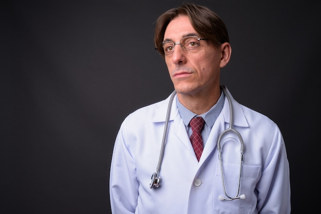 Зрелый красивый итальянский мужчина доктор против серой стены