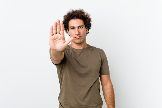 Mature handsome man standing with outstretched hand showing stop sign, preventing you.