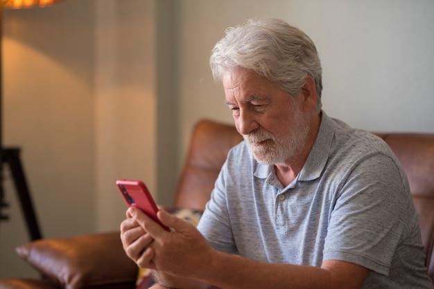 成熟したハンサムな男性のテキストとスマートフォンでのメッセージの書き込み-高齢者は携帯電話を使用して自宅のソファに座ってチャットします-1人の退職者は接続されたデバイスで一人で屋内ライフスタイル