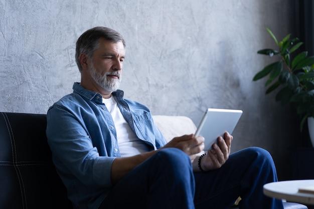 自宅でタブレットで成熟したハンサムな男websurfing。