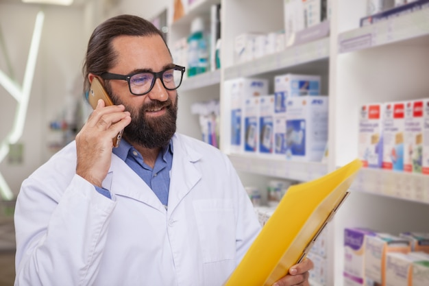 Mature handsome pharmacist answering calls, working at drugstore