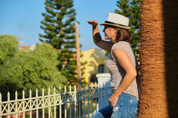 日没のヤシの木の近くに立っているサングラス帽子の成熟した幸せな美しい女性