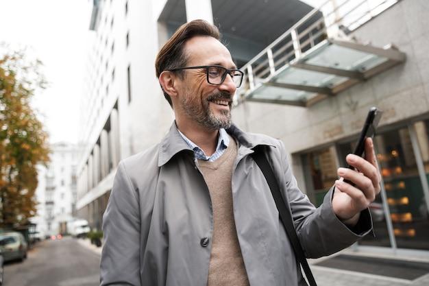 Зрелый счастливый бизнесмен в очках с помощью мобильного телефона и улыбается, стоя возле офисного здания на городской улице