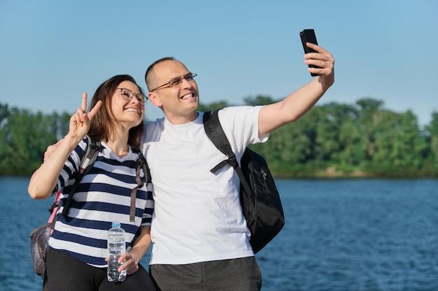 電話でselfie写真を撮る成熟した幸せなカップル