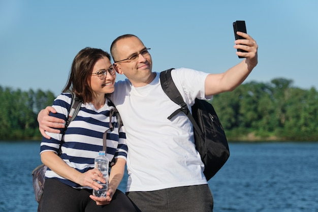 Mature happy couple taking selfie photo on phone