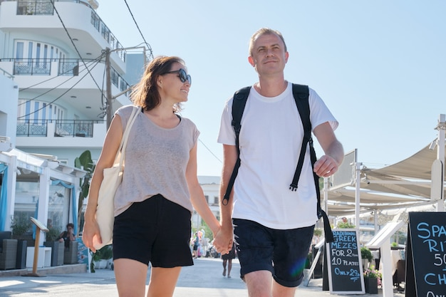 Mature happy couple walking around resort town holding hands. communication, lifestyle, travel, outdoor activities for middle-aged people