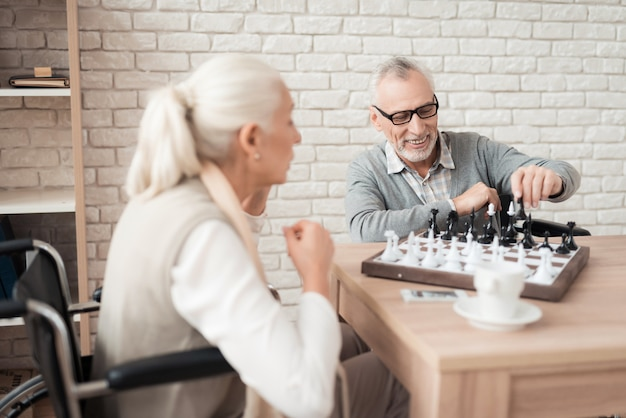 Mature happy couple in wheelchairs play chess.