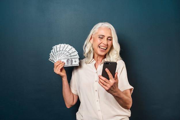 携帯電話を使用してお金を保持している成熟した幸せな老婦人。