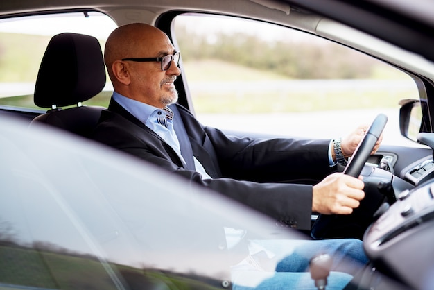 スーツで成熟した幸せなプロのエレガントなビジネスマンが車を運転しています。