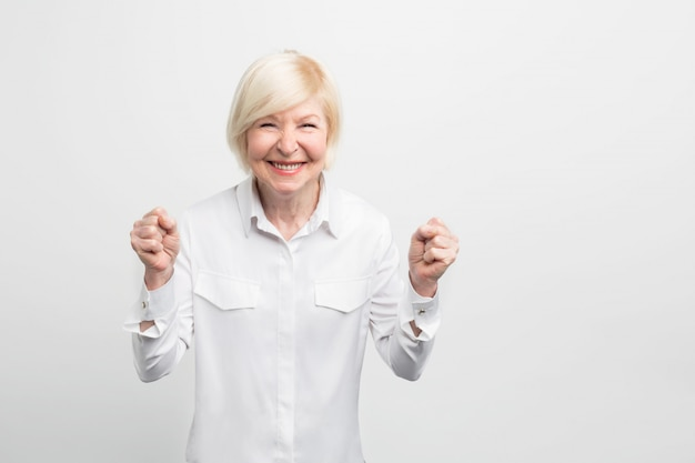 Mature and happy woman is rejoicing. despiced she is old she is quite confident and feminine at the same time.