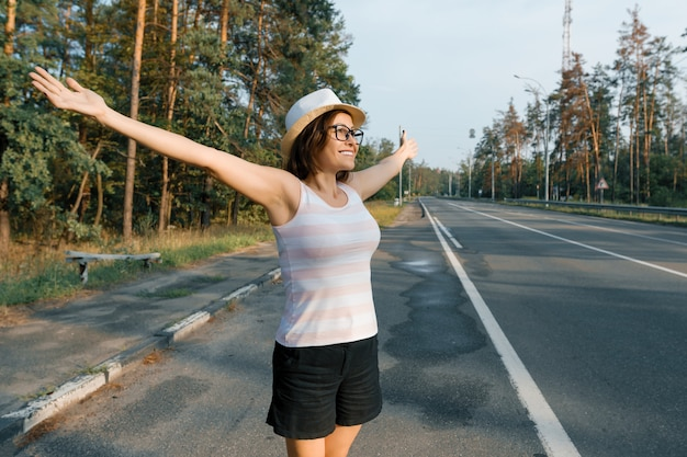 Mature happy woman standing on the road, smiling open arms to the sun