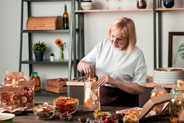 乾燥したオレンジ、ナシ、柿、キウイ、イチゴを台所のテーブルで紙の小包に詰める成熟した主婦