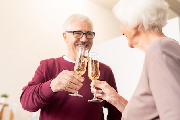 Зрелые муж и жена чокаются бокалами шампанского на домашней вечеринке